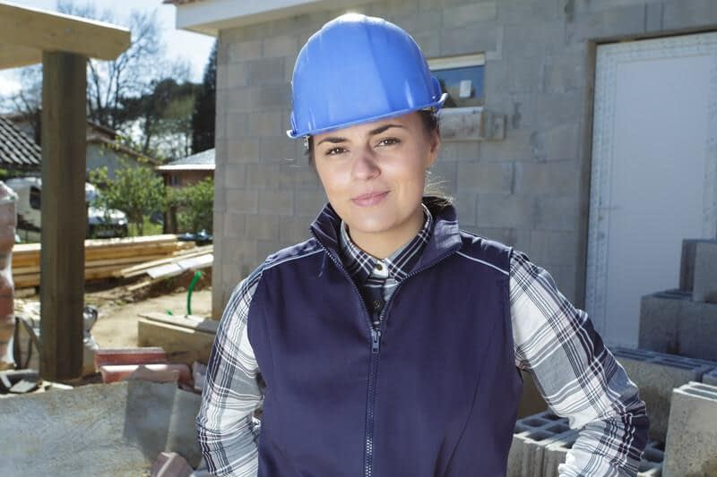 A young woman wearing a construction hat works at a site surrounded by bricks.