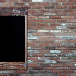 A wall of brick with a wooden framed window.